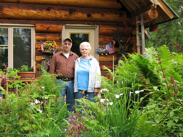 Judy and Larry Heilman pose in front of their Beluga homestead. They are fighting to keep their home of 24 years coal-free. Photo courtesy of Alaskans First.