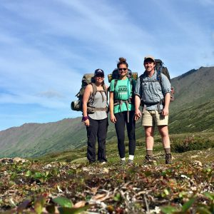 Three hikers stand in front of hills and blue skies in the Chugach Range, Alaska