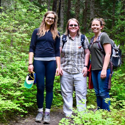 Kat, Catherine and Hannah stand on the Winner Creek Trail in Girdwood with lots of green leaves