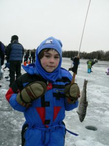 Tracy's son Lucas holding a fish after ice fishing.