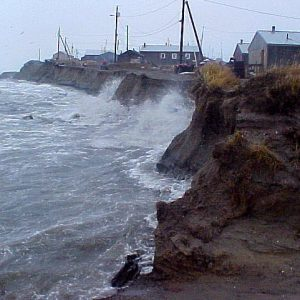 Photos of waves watching against an eroding wall of dirt with house precariously close to the edge. Climate change harms Alaska's coastal communities.