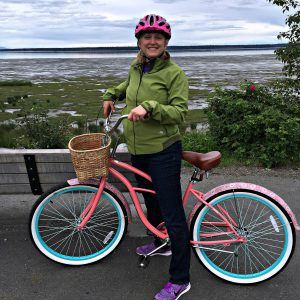 Tracy posing with her bike with the mud flats of Cook Inlet behind her.