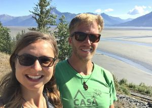 Kat and Dave take a photo with the Turnagain Arm mudflats and blue skies behind them.