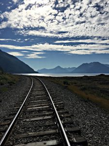 Hiking and biking into wilderness inspire taking heart in the wild. Here, train tracks reach toward a blue sky along Turnagain Arm.
