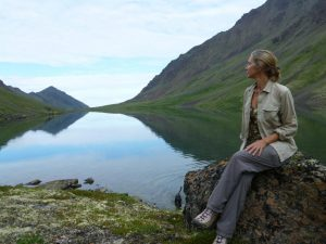 Marybeth sitting in front of a long lake with reflection of mountains.