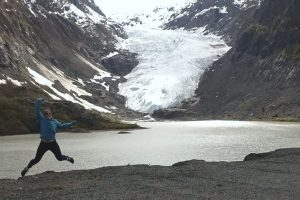 Michelle's jumping in front of a lake with a glacier in the background.