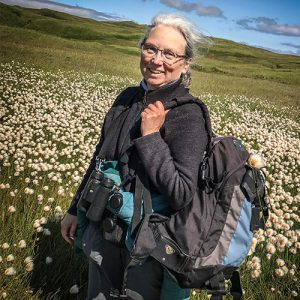 A photo of Nancy Lord in a field of wild flowers and grasses