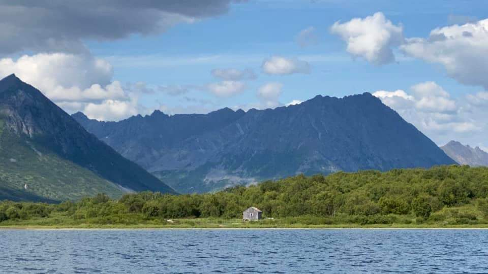 The family cabin on Togiak Lake with mountains behind it, water in front, blue skies above. Take care of the land and it will take care of you.