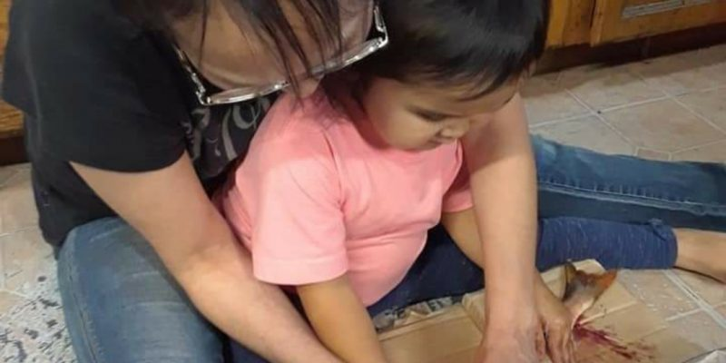 Fannie teaches her grandbaby to split fish using a uluaq or ulu knife.