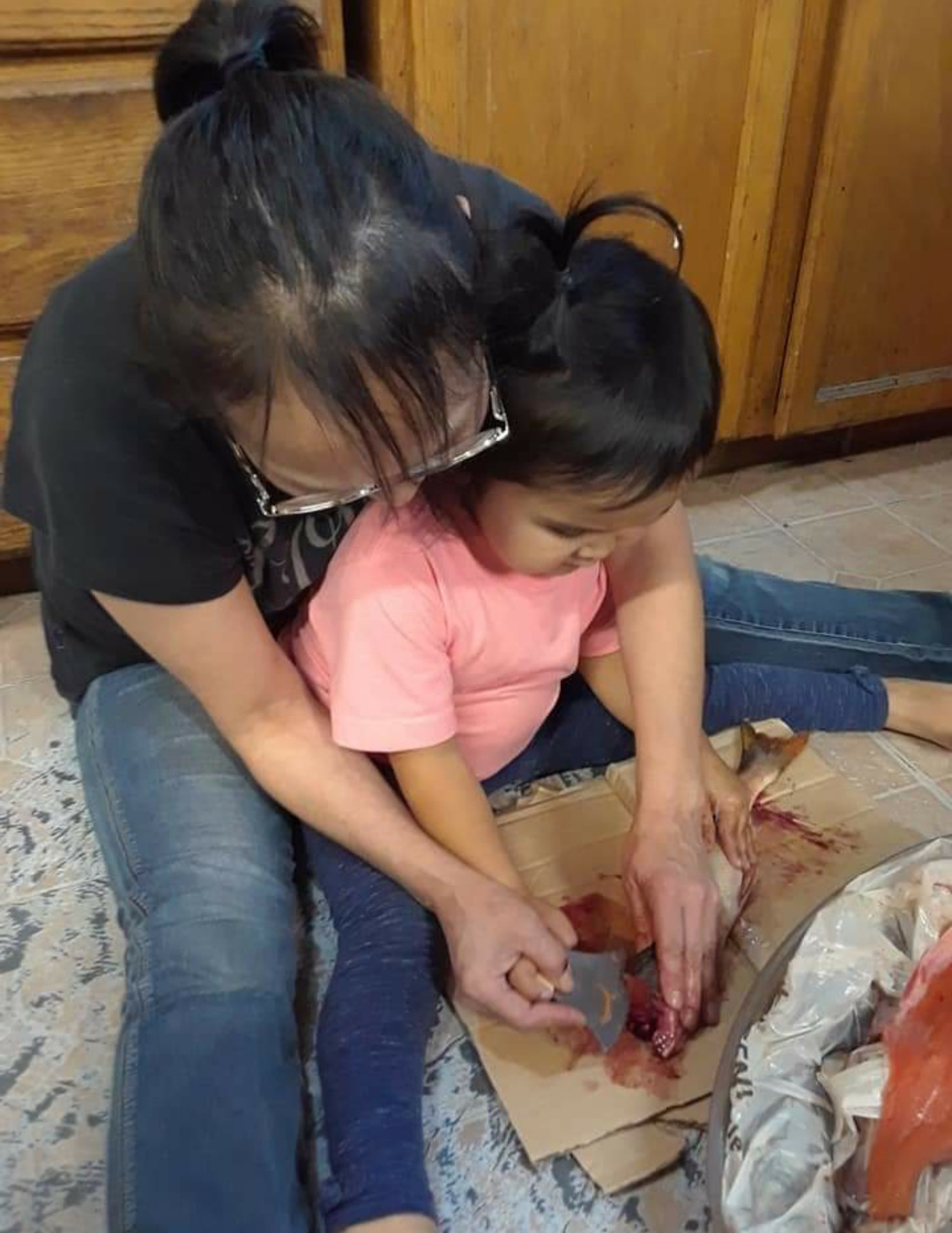 Fannie teaches her grandbaby to split fish using a uluaq or ulu knife.