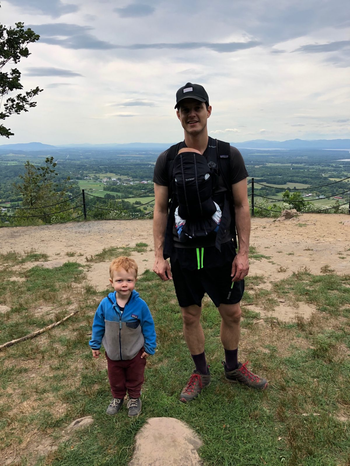 Carl and his kids on a hill with sky in the background in Vermont, 2020