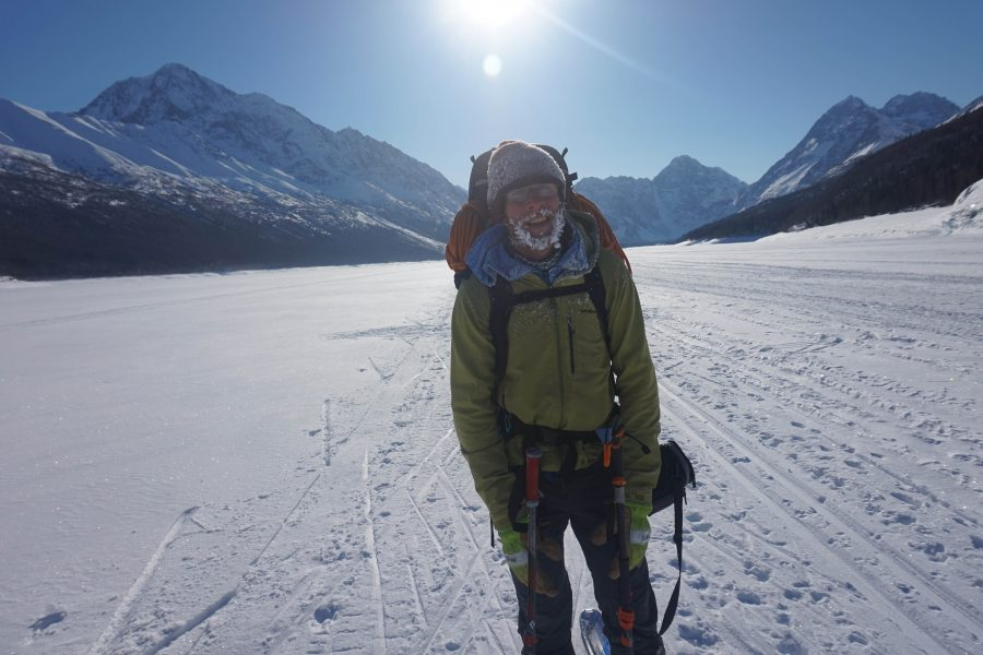 Lang with a pack on skis with the mountains and sun behind him.
